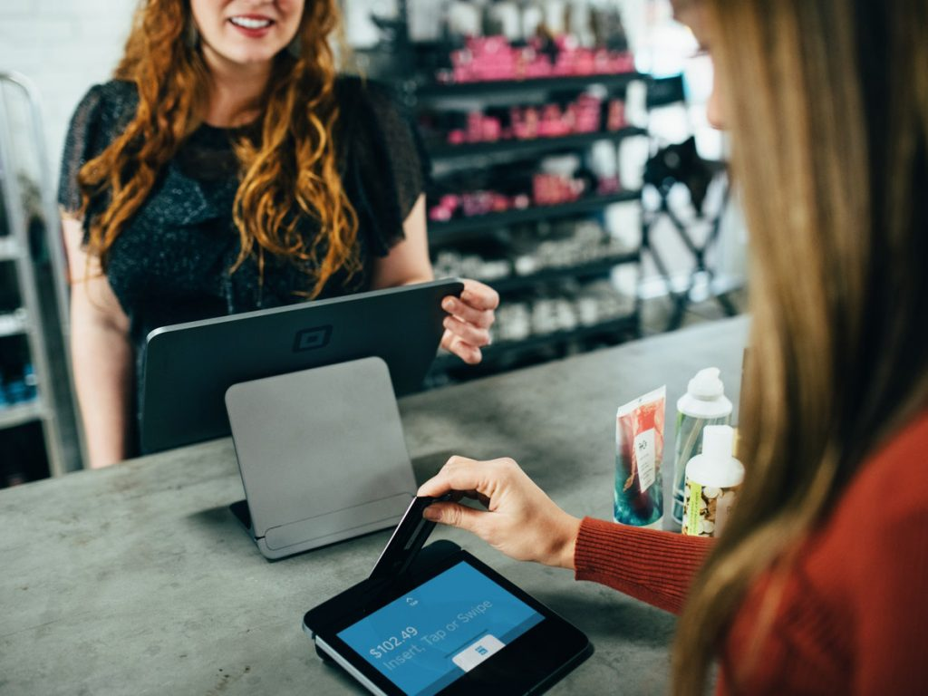Music for business red hair girl checking out another girl with her tablet while the customer is inserting a credit card
